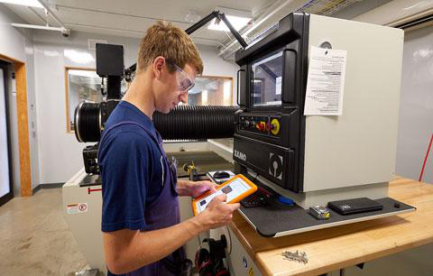 CWRU student looking at screen controls for a piece of fabricating equipment at think[box]
