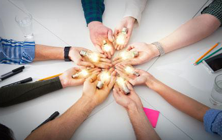 Artistic photo of nine people stretching their arms toward each other with a lightbulb in each hand