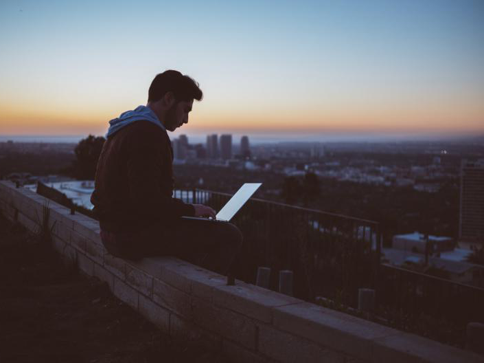 guy on roof on laptop